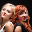 Two happy young girlfriends black background - Stock Photo