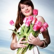 Smiling woman with bunch of flowers — Stock Photo