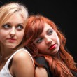 Two happy young girlfriends black background — Stock Photo