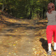 Womwalking cross country trail in autumn forest — стоковое фото #27178049