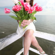 Smiling woman with bunch of flowers sea — Stock Photo