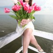 Stock Photo: Smiling womwith bunch of flowers sea
