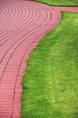 Camino de piedra jardín con césped, acera de ladrillo — Foto de Stock