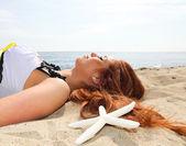Het mooie meisje ligt aan zeekust — Stockfoto