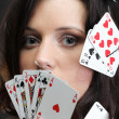 Woman holding playing cards black background — Stock Photo