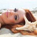 The beautiful girl lies on sea coast — Stock Photo