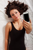 Sexy lazy girl lying with phone on bed in bedroom — Stock Photo