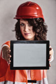 Sexy girl in safety helmet showing tablet — Stock Photo