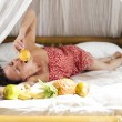 The girl on bed eating fruits — Stock Photo