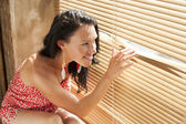 Young brunette looking out the window through the blinds — Stock Photo