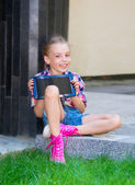 Young girl sitting with a tablet in hands in the schoolyard — Stock Photo