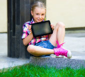 Young girl sitting with a tablet — Stock Photo
