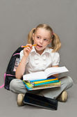 Schoolgirl with books makes homework. — Stock Photo