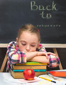Portrait of sad schoolgirl with books and apple. School concept. — Stock Photo