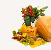 Harvested pumpkins with autumn leaves, chestnuts, rosehip, candle — Stock Photo