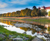 Autumn city landscape with reflection in the river — Stock Photo