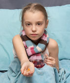 Sick child with pills and a cup of herbal tea — Stock Photo