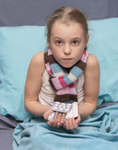 Sick child with pills in hand — Stock Photo