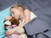 Child sleeping with her a favorite toy — Стоковое фото