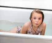 Little girl bathes in a bathroom. — Stock Photo