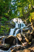 Beautiful little waterfall with several cascades over large ston — Stock Photo