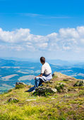 Man sitting and looking at mountains — Stock Photo