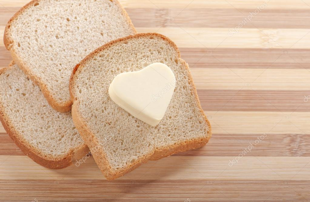 Healthy eating concept - piece of wheat bread with a heart shaped symbol of butter — Stock Photo #18635987