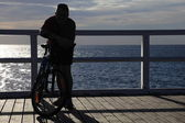 Man with a Bike at the pier, jetty in morning sea — Stock Photo