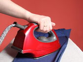 Household chores - red iron in hand and navy blue shir — Stock Photo