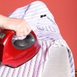 Household chores - red iron in hand and white shirt — Stock Photo