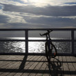 Bike at the pier, jetty in morning sea - Stock Photo