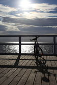 Bike at the pier, jetty in morning sea — Stock Photo