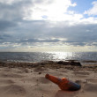 Bottle on beach sea and sky - Stock Photo