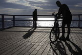 Man with Bike at the pier, jetty in morning sea — Stock Photo