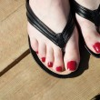 Female feet with flip-flops red nail - Foto Stock