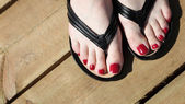 Female feet with flip-flops red nail — Stock Photo