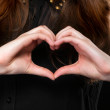 Stock Photo: Girl doing heart shape love symbol with her hands.
