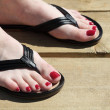 Stock Photo: Female feet with flip-flops red nail
