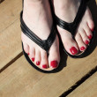 Female feet with flip-flops red nail — Stock Photo #26222199