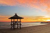 Beautiful sunset on the beach and beach hut — Stock Photo