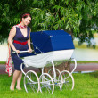Pretty young mother  in the  park with a stroller — Stock Photo