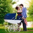 Family in the park with a stroller — Stock Photo