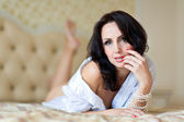 Beautiful woman lying on the bed — Stock Photo