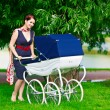 Beautiful young mother with a stroller — Stok fotoğraf