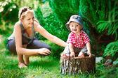 Carino piccolo ragazzo seduto su un ceppo con mamma — Foto Stock
