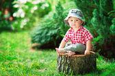 Ładny mały chłopiec siedzi na pniu drzewa — Zdjęcie stockowe