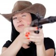 Girl in a hat with a gun aiming — Stock Photo