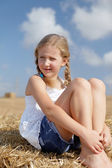 Blond girl on a haystack — Stock Photo