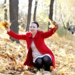 Happy girl playing with autumn leaves — Stock Photo #13925417