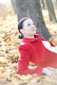 Rapariga bonita sentada em folhas de outono — Foto Stock